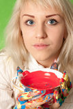 Aantrekkelijk meisje met kleurrijke handen een kop van rode verf Stock Foto's