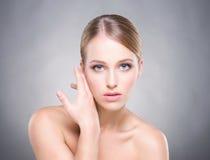 Aantrekkelijk meisje met vlotte huid over de grijze achtergrond stock afbeeldingen