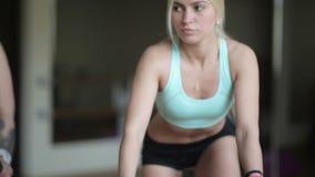 Aantrekkelijk meisje op een hometrainer stock videobeelden