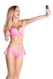 Aantrekkelijk meisje in roze zwempak die selfie op de telefoon nemen royalty-vrije stock foto