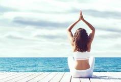 Aantrekkelijk meisje in witte sportieve kleren die yoga op een houten pijler doen Yoga, sport, vrije tijd, recreatie en vrijheid Stock Foto's