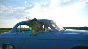 Aantrekkelijk meisje in zonnebril die uit uitstekend autoraam leunen en van reis genieten Jonge paarreis op retro auto binnen stock footage