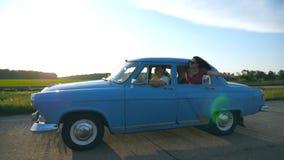 Aantrekkelijk meisje in zonnebril die uit uitstekend autoraam leunen en van reis genieten Jonge paarreis op retro auto binnen stock video