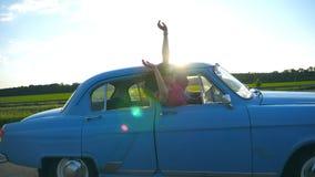 Aantrekkelijk meisje in zonnebril die uit uitstekend autoraam leunen en van reis genieten Jonge paarreis op retro auto binnen stock videobeelden