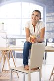 Aantrekkelijk meisjesdagdromen bovenop bureau het glimlachen Stock Afbeelding