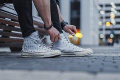 Aantrekkelijk mensen bindend kant van zijn witte tennisschoenen en het zitten op bank stock foto