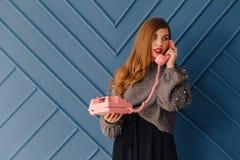 Aantrekkelijk modieus jong meisje met retro roze telefoon op aqua achtergrondemoties stock afbeelding