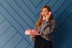 Aantrekkelijk modieus jong meisje met retro roze telefoon op aqua achtergrondemoties royalty-vrije stock foto
