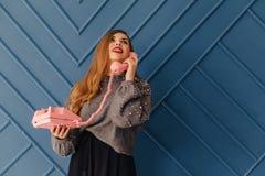 Aantrekkelijk modieus jong meisje met retro roze telefoon op aqua achtergrondemoties stock foto's