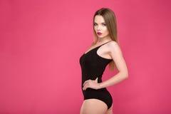 Aantrekkelijk mooi model in het zwarte zwempak stellen op roze achtergrond Royalty-vrije Stock Foto's