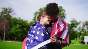 Aantrekkelijk multi-etnisch paar die elkaar omhelzen die Amerikaanse vlag op de achter status op het groene gebied houden stock video