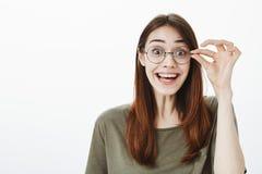 Aantrekkelijk nerdy die meisje wordt gefascineerd om nieuw boek in opslag te zien Knappe overweldigde vrouw in toevallige t-shirt royalty-vrije stock foto's