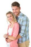 Aantrekkelijk paar die en bij camera omhelzen glimlachen Royalty-vrije Stock Afbeeldingen