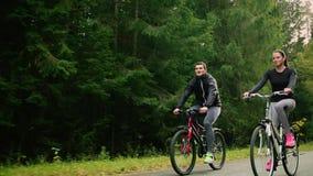 Aantrekkelijk paar die met fietsen en drinkwater in het bos lopen stock video