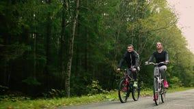 Aantrekkelijk paar die met fietsen en drinkwater in het bos lopen stock footage
