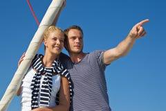 Aantrekkelijk paar op varende boot: mens die met wijsvinger richten Stock Foto