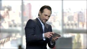 Aantrekkelijk rijp zakenman speelspel op telefoon stock footage