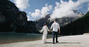 Aantrekkelijk romantisch paar die hun handen houden lopend onderaan het strand Langzame Motie Rood Heldendicht stock video