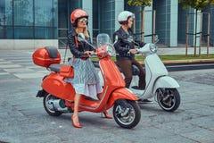 Aantrekkelijk romantisch paar, een knappe mens en een sexy wijfje, die zich met twee retro Italiaanse autopedden tegen a bevinden stock fotografie