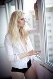 Aantrekkelijk sexy blonde die met wit overhemd op het venster in daglicht kijken Portret van sensuele lange eerlijke haarvrouw di Royalty-vrije Stock Foto's