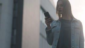 Aantrekkelijk verbazend meisje met blonde die met donkerrode lippen in blauw denimhof en strikte bluse sommige acties uitvoeren stock video