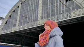 Aantrekkelijk volwassen meisje dat in blauwe laag en kleurrijke hoed op iemand bij het station wacht stock videobeelden