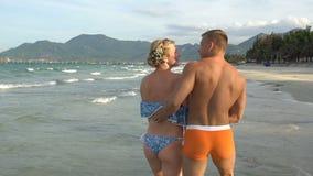 Aantrekkelijk vrolijk paar die bij strand lopen Omhelzing elkaar en kus