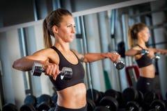 Aantrekkelijk vrouwengewichtheffen bij de gymnastiek stock foto