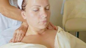 Aantrekkelijk wijfje bij kuuroordgezondheidsclub die een gezichtsprocedure en een massage krijgen Royalty-vrije Stock Afbeeldingen