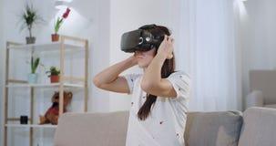 Aantrekkelijk wijfje die een virtuele werkelijkheidsglazen dragen terwijl het zitten op de klaar bank, wil zij rond reizen stock video