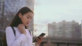 Aantrekkelijk wijfje die mobiele telefoon in langzame motie met behulp van Het meisje maakt haar haar recht stock video
