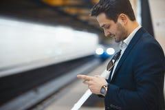 Aantrekkelijk zakenman texting bericht in mobiele telefoon terwijl het wachten op trein in metro royalty-vrije stock afbeelding