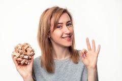 Aantrekkelijke 24 éénjarigen bedrijfsvrouw kijken die die met houten raadsel wordt verward Stock Afbeeldingen