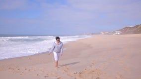 Aantrekkelijke actieve hogere vrouw die op het verlaten oceaanstrand lopen stock video