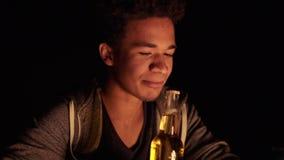 Aantrekkelijke Afrikaanse Amerikaan die een bierfles met tanden openen en het geven aan zijn meisje terwijl het zitten door stock video
