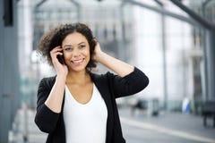 Aantrekkelijke Afrikaanse Amerikaanse bedrijfsvrouw die met cellphone glimlachen Stock Foto's