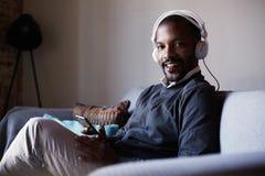 Aantrekkelijke Afrikaanse Amerikaanse mens die met witte hoofdtelefoons aan muziek op zijn telefoon luisteren Concept ontspanning stock fotografie