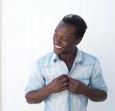 Aantrekkelijke Afrikaanse Amerikaanse mens het aanpassen overhemdsknoop in openlucht Royalty-vrije Stock Afbeelding