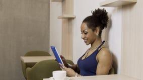 Aantrekkelijke afro vrouwelijke persoon die terwijl het gebruiken van tablet in handen glimlachen stock footage