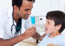 Aantrekkelijke arts die geneeskunde geeft aan een kleine jongen Royalty-vrije Stock Foto