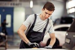 Aantrekkelijke automechanic poetst een auto bij zijn werk op De autodienst en onderhoud royalty-vrije stock foto