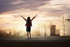 Aantrekkelijke Aziatische bedrijfsvrouw die zich op een rand een dak bevinden Stock Foto