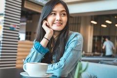 Aantrekkelijke Aziatische vrouw het drinken koffie vrolijke meisje het drinken koffie of thee in ochtend stock foto
