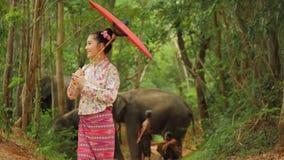 Aantrekkelijke Aziatische vrouw in traditioneel zuidoostaziatisch kostuum die op aardachtergrond dansen stock video
