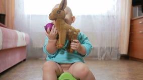 Aantrekkelijke babyzitting op de pot en het spelen met teddy herten In de handen van de de Nieuwjaar` s bal en decoratie voor stock videobeelden