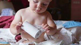 Aantrekkelijke babyzitting op een bed en tearing toiletpapier Jong geitje 1 jaar stock videobeelden
