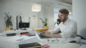 Aantrekkelijke bedrijfsmens die op het kantoor werken en fotokader bekijken stock videobeelden