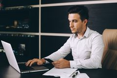 Aantrekkelijke bedrijfsmens in slimme vrijetijdskledingszitting op zijn werkende plaats in bureau stock foto's