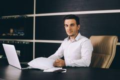 Aantrekkelijke bedrijfsmens in slimme vrijetijdskledingszitting op zijn werkende plaats in bureau Stock Afbeeldingen