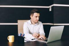 Aantrekkelijke bedrijfsmens in slimme vrijetijdskledingszitting op zijn werkende plaats in bureau stock fotografie